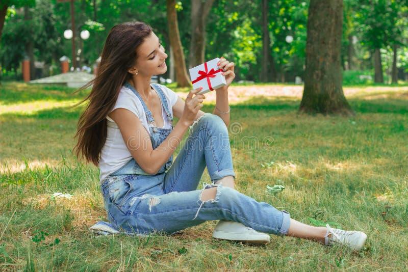 Het vrolijke jonge meisje zit op een gras met gift in haar handen stock foto