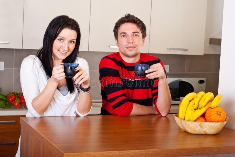 Het vrolijke jonge paar drinkt koffie royalty-vrije stock afbeelding