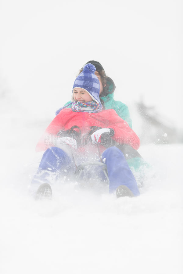 Het vrolijke jonge paar sledding in sneeuw royalty-vrije stock afbeelding