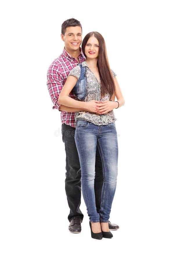 Het vrolijke jonge paar stellen op witte achtergrond stock afbeelding