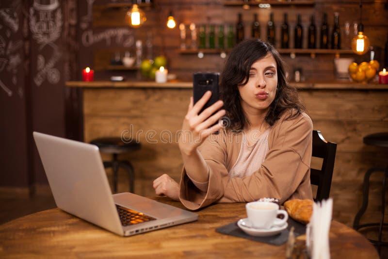 Het vrolijke jonge vrouw knipogen de camera in een koffiewinkel stock afbeeldingen