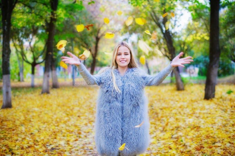 Het vrolijke jonge vrouw spelen met de herfstbladeren stock fotografie