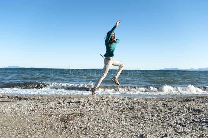 Het vrolijke jonge vrouw spelen op het strand stock fotografie