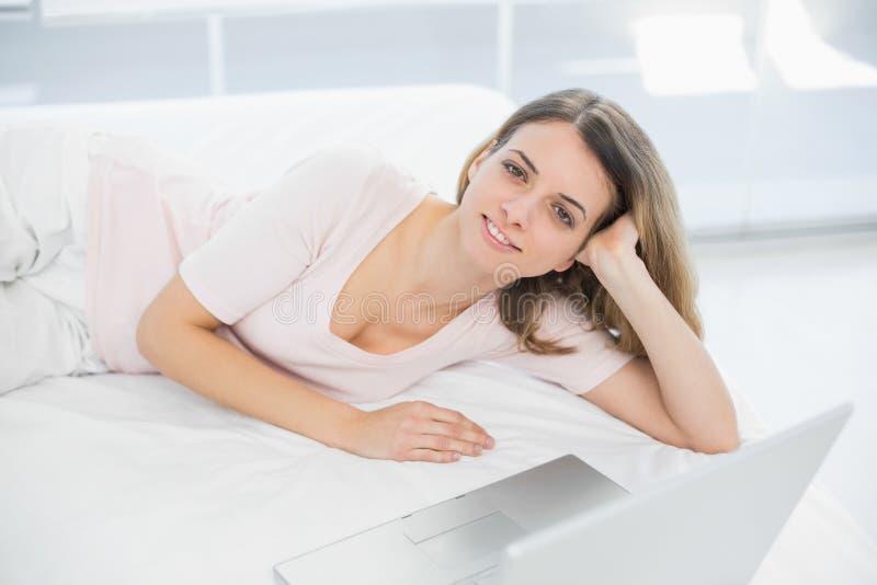 Het vrolijke jonge vrouw stellen die op haar bed liggen die bij camera glimlachen royalty-vrije stock foto