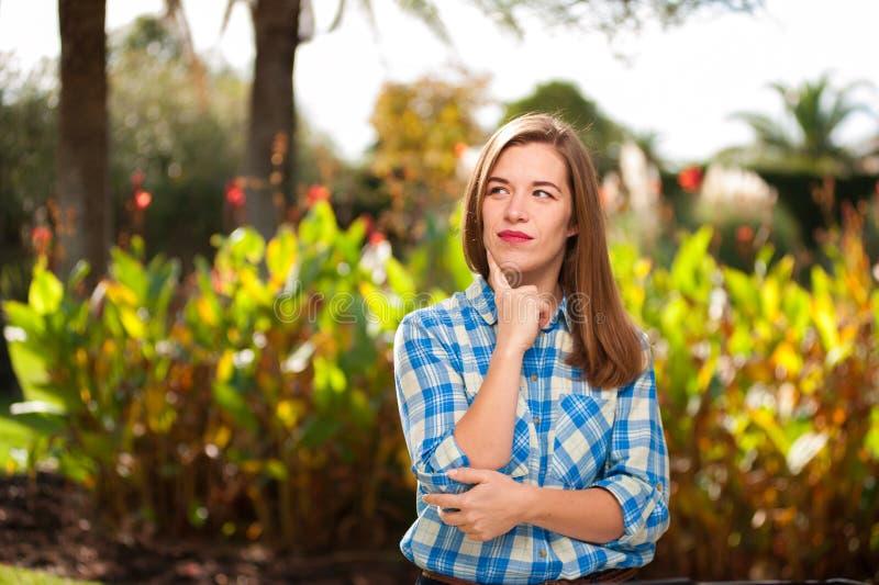 Het vrolijke jonge vrouw stellen tegen de zomerpark stock fotografie