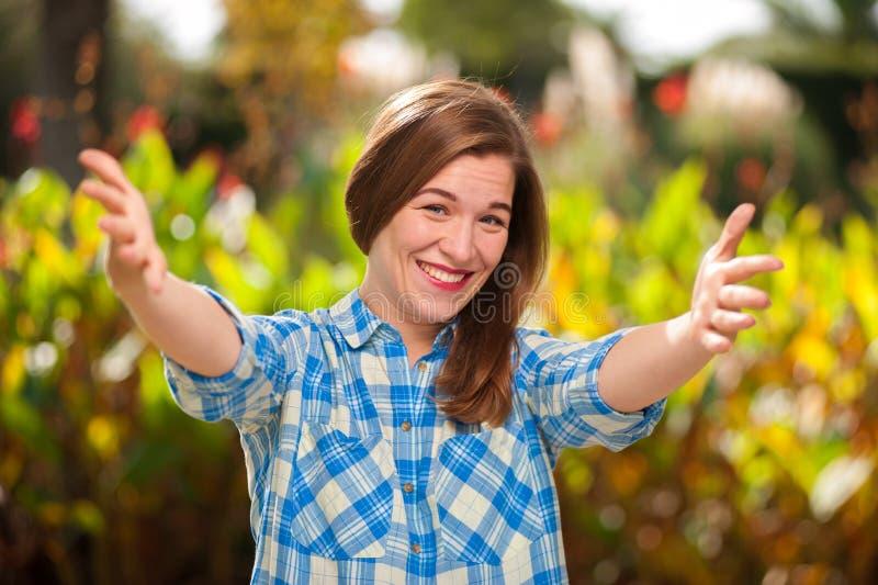 Het vrolijke jonge vrouw stellen tegen de zomerpark stock foto's