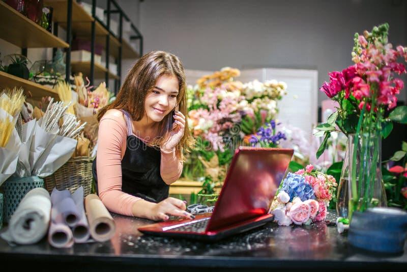 Het vrolijke jonge vrouwelijke bloemistwerk aangaande laptop Zij spreekt op telefoon en glimlach Jonge vrouwentribune in ruimteho royalty-vrije stock afbeelding