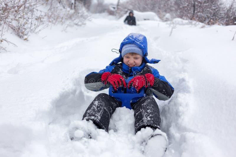 Het vrolijke jongen sledding royalty-vrije stock afbeeldingen