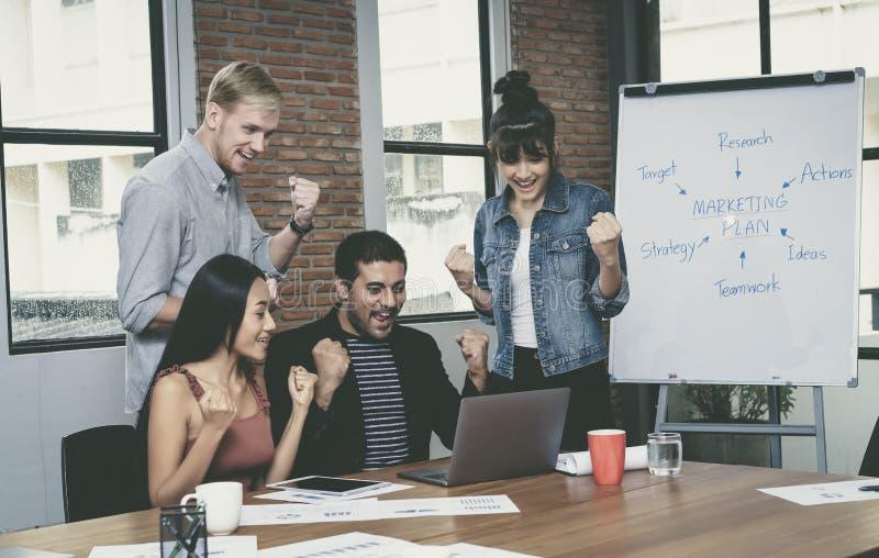 Het vrolijke jongeren commerciële team in modern bureau viert s royalty-vrije stock afbeeldingen