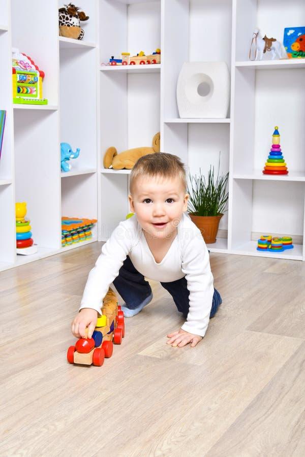 Het vrolijke kind spelen met een trein royalty-vrije stock afbeelding