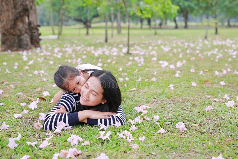 Het vrolijke kindmeisje knuffelt haar mamma volledig liggend op groen gebied met dalings roze bloem in de tuin openlucht Gelukkig stock afbeelding