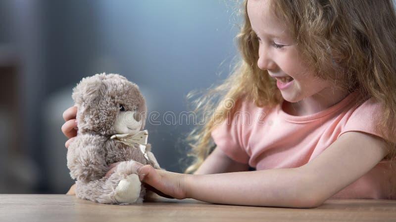 Het vrolijke krullende blonde meisje spelen met teddybeer en het lachen, vrije tijdsactiviteit royalty-vrije stock afbeelding