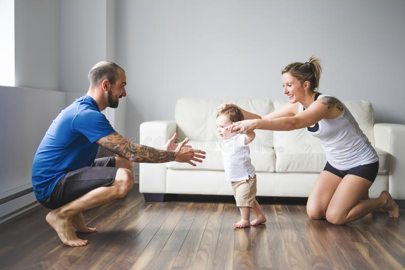 Het vrolijke mamma en de papa helpen hun zoon thuis te lopen royalty-vrije stock foto's