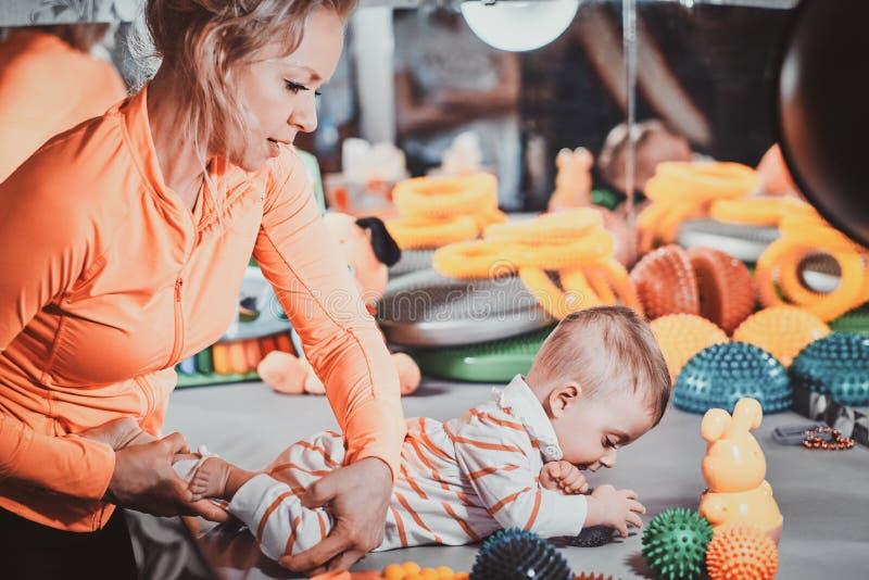 Het vrolijke mamma plaing met haar pasgeboren baby bij masseurkabinet royalty-vrije stock foto's
