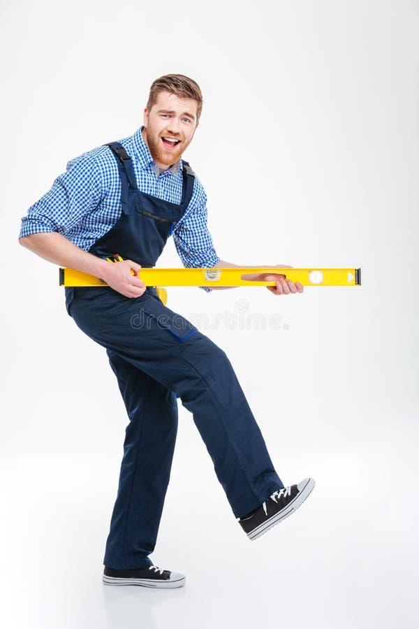 Het vrolijke mannelijke bouwer spelen met waterpas royalty-vrije stock foto