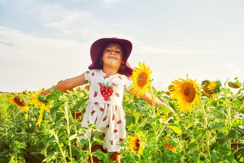 Het vrolijke meisje in a breed-brimmed hoed het spelen op het gebied met zonnebloemen royalty-vrije stock afbeeldingen
