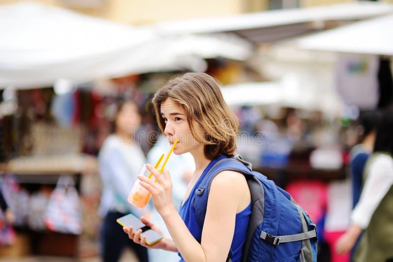 Het vrolijke meisje drinkt sap op de straat van Rome stock foto's