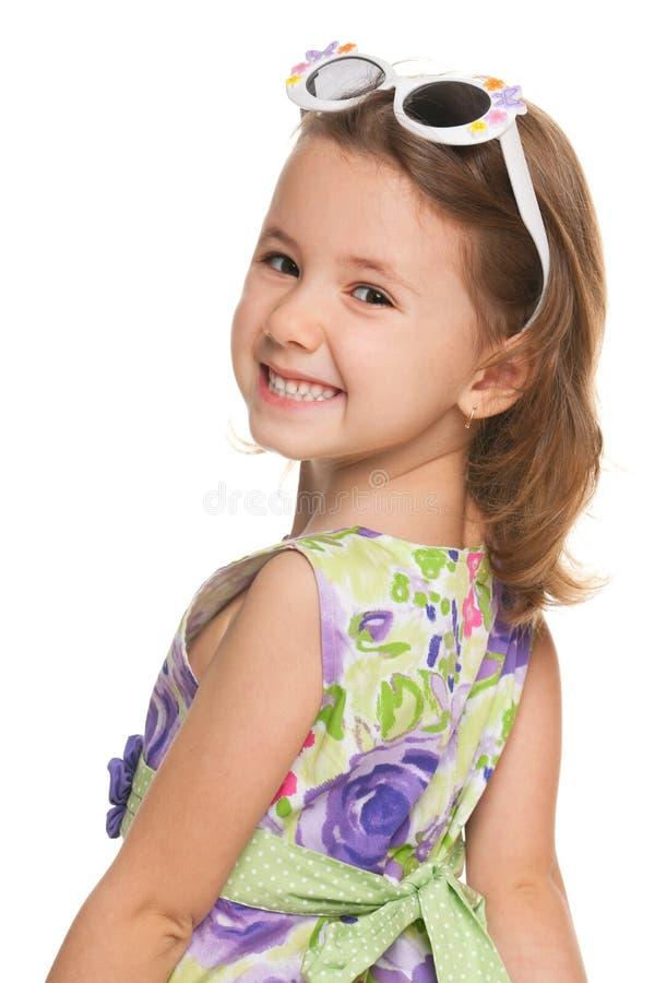 Het vrolijke meisje kijkt terug stock fotografie