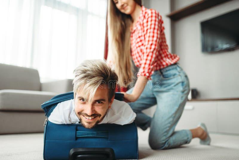 Het vrolijke meisje pakte haar echtgenoot in een koffer in royalty-vrije stock fotografie