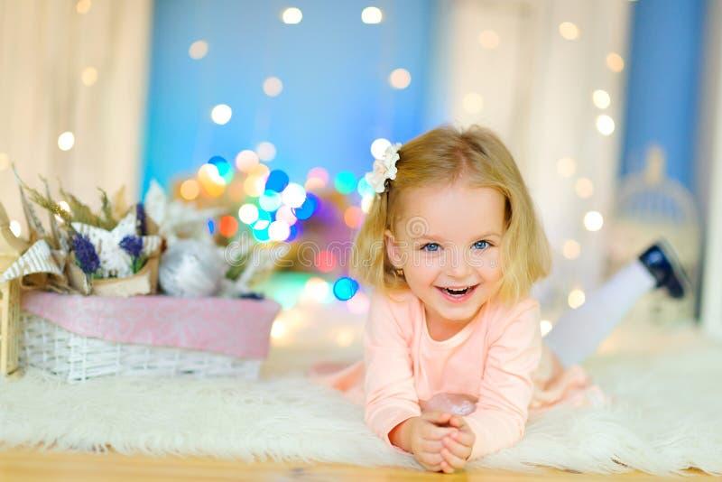 Het vrolijke meisje spelen die op de vloer liggen royalty-vrije stock afbeeldingen