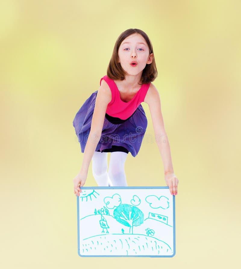 Het vrolijke meisje toont haar tekening stock afbeelding
