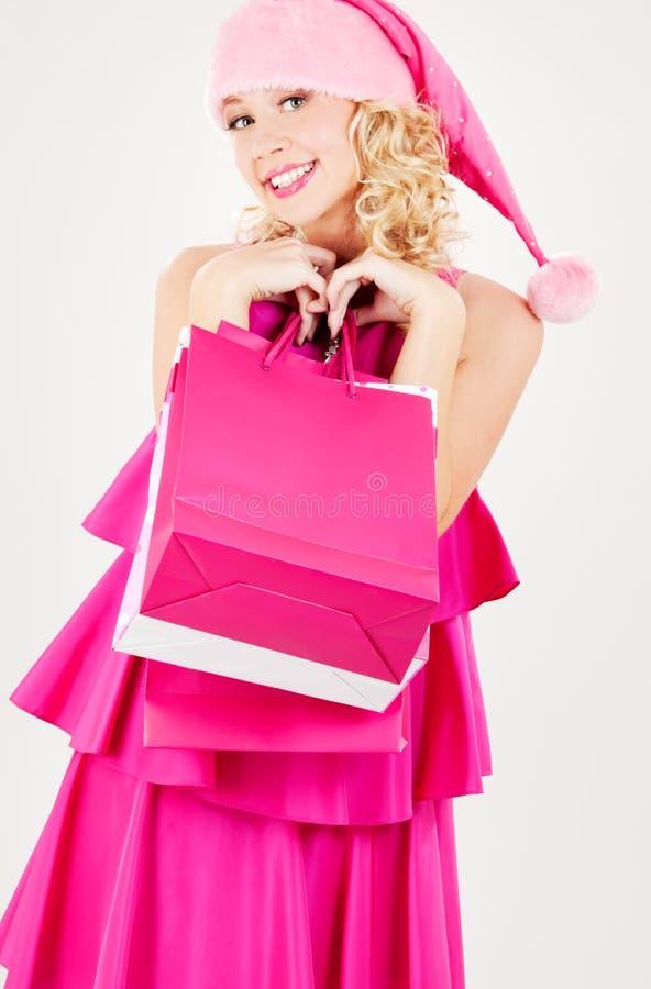 Het vrolijke meisje van de santahelper met het winkelen zakken stock afbeeldingen