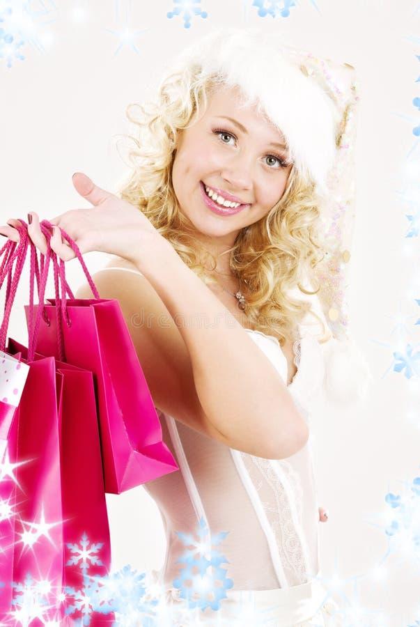 Het vrolijke meisje van de santahelper met het winkelen zakken stock foto