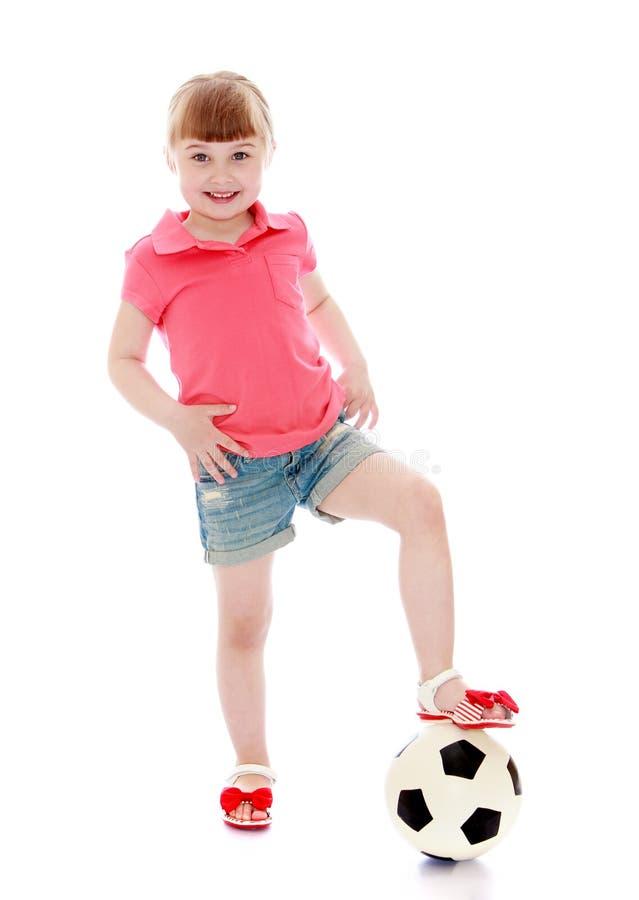 Het vrolijke meisje zette haar voet op een voetbalbal stock afbeeldingen