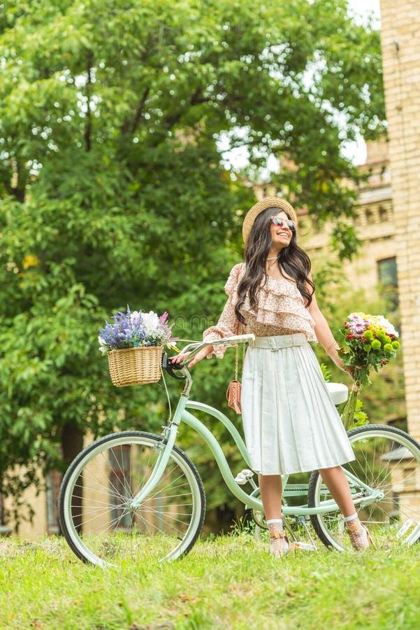 het vrolijke modieuze donkerbruine meisje stellen dichtbij fiets met bloemen royalty-vrije stock fotografie