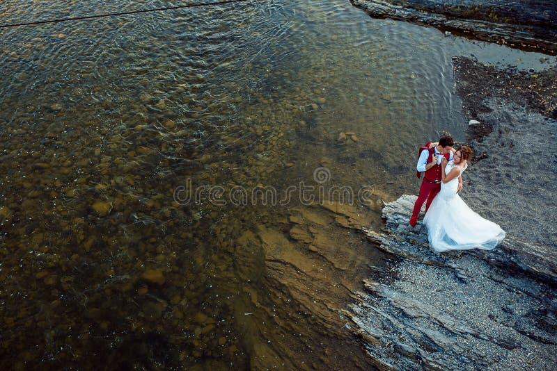 Het vrolijke modieuze jonggehuwdepaar koestert op de rivierbank tijdens de zonnige dag Boven mening royalty-vrije stock afbeeldingen