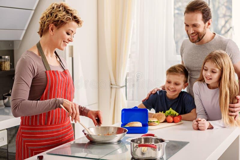 Het vrolijke moeder koken voor haar familie stock fotografie