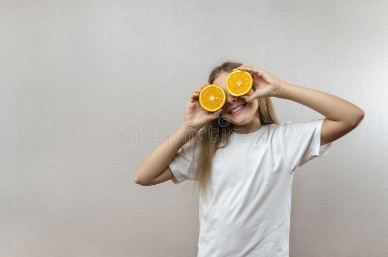 Het vrolijke mooie meisje houdt in de helften oranje helften Positieve emoties Gezond voedsel Veggie en Veganist stock afbeeldingen