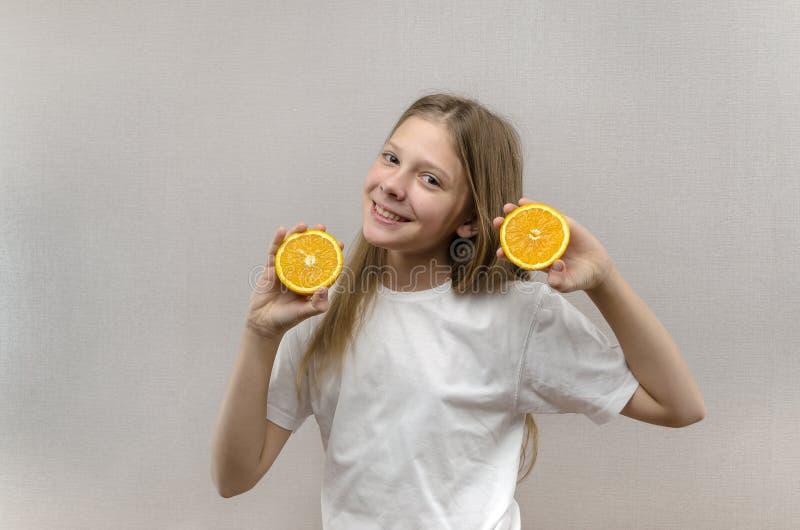 Het vrolijke mooie meisje houdt in de helften oranje helften Positieve emoties Gezond voedsel Veggie en Veganist stock foto