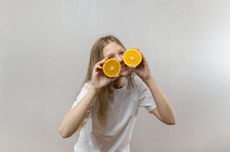 Het vrolijke mooie meisje houdt in de helften oranje helften Positieve emoties Gezond voedsel Veggie en Veganist royalty-vrije stock foto