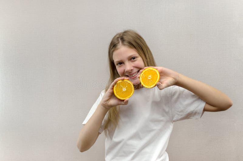 Het vrolijke mooie meisje houdt in de helften oranje helften Positieve emoties Gezond voedsel Veggie en Veganist royalty-vrije stock afbeelding