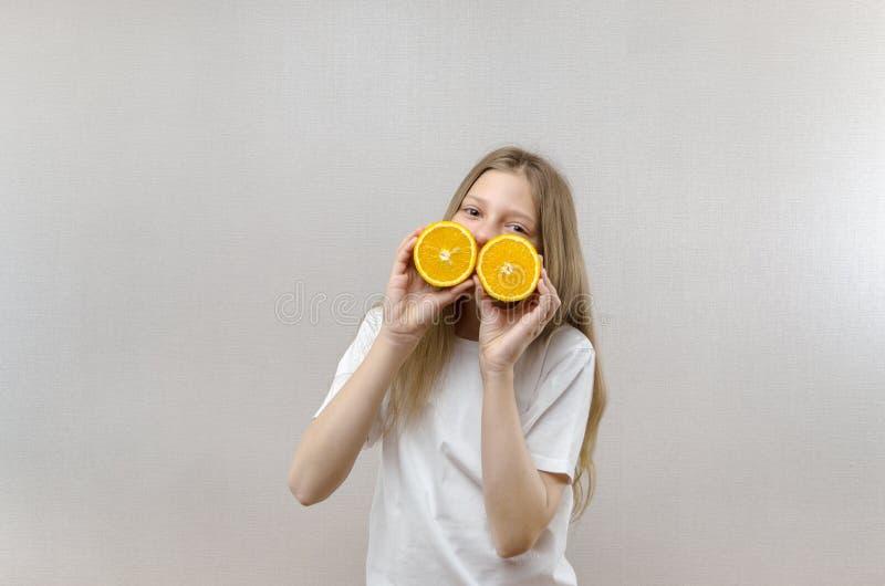 Het vrolijke mooie meisje houdt in de helften oranje helften Positieve emoties Gezond voedsel Veggie en Veganist stock afbeelding