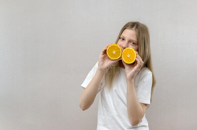 Het vrolijke mooie meisje houdt in de helften oranje helften Positieve emoties Gezond voedsel Veggie en Veganist royalty-vrije stock afbeeldingen