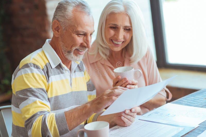 Het vrolijke oude paar die hun zaken bespreken is thuis van belang stock foto