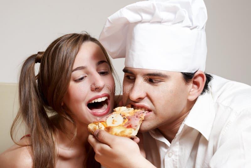 Het vrolijke paar dat een pizza eet royalty-vrije stock foto
