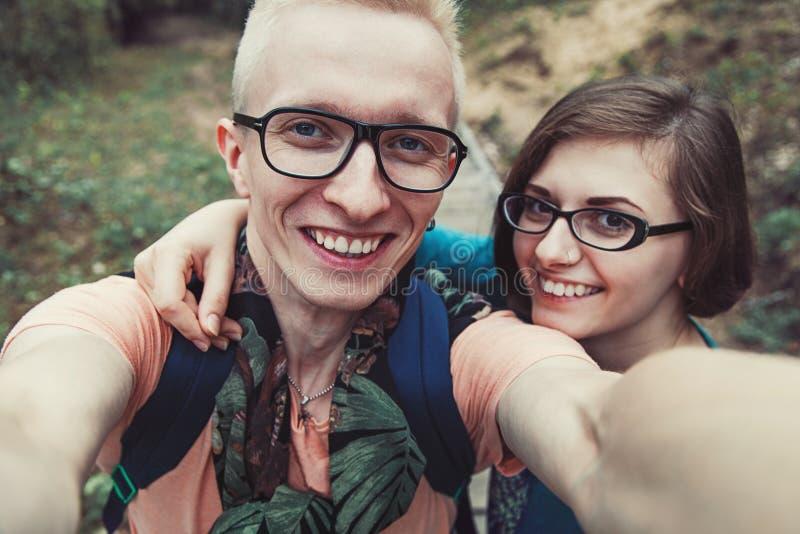 Het vrolijke paar in glazen maakt in openlucht selfe stock afbeeldingen