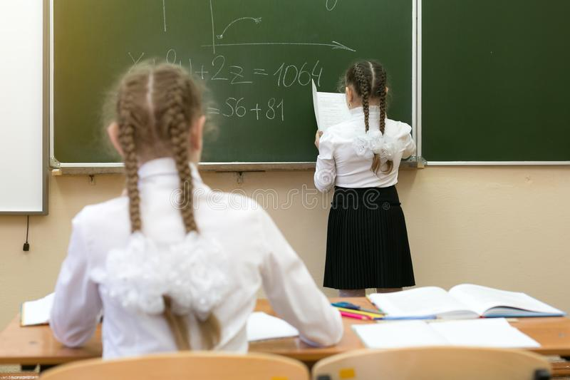 Het vrolijke schoolmeisje stelt in een les tevreden royalty-vrije stock afbeelding
