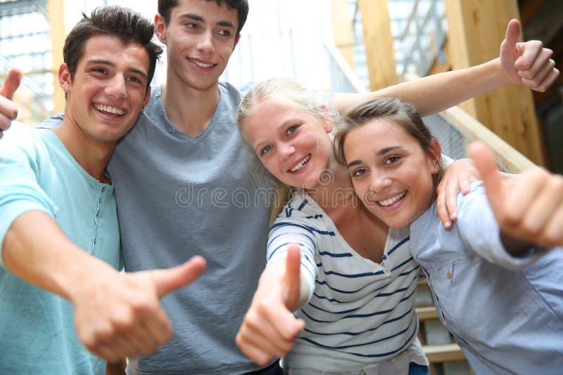 Het vrolijke studenten tonen beduimelt omhoog royalty-vrije stock afbeelding
