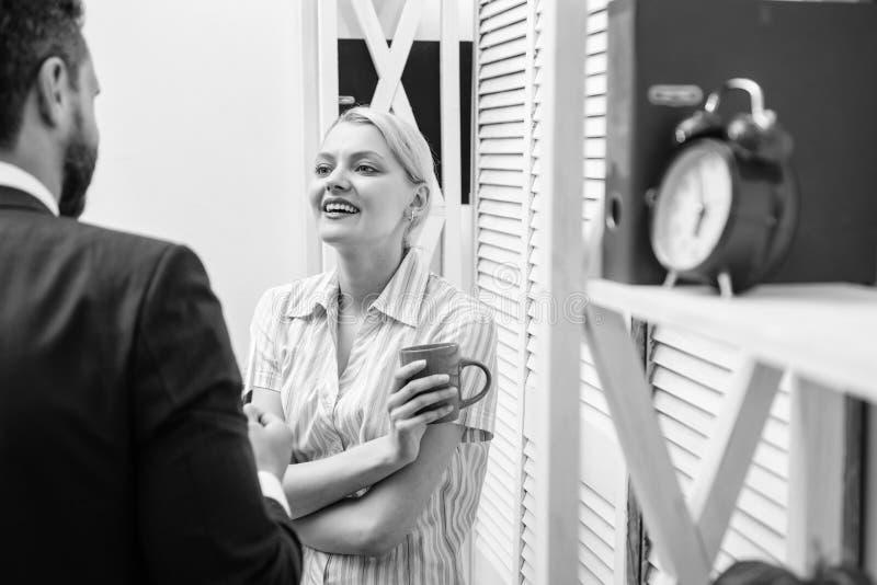 Het vrolijke werk van twee mensen tijdens onderbrekingstijd in helder bureau Commercieel team die koffiepauze, bespreking hebben  royalty-vrije stock foto's
