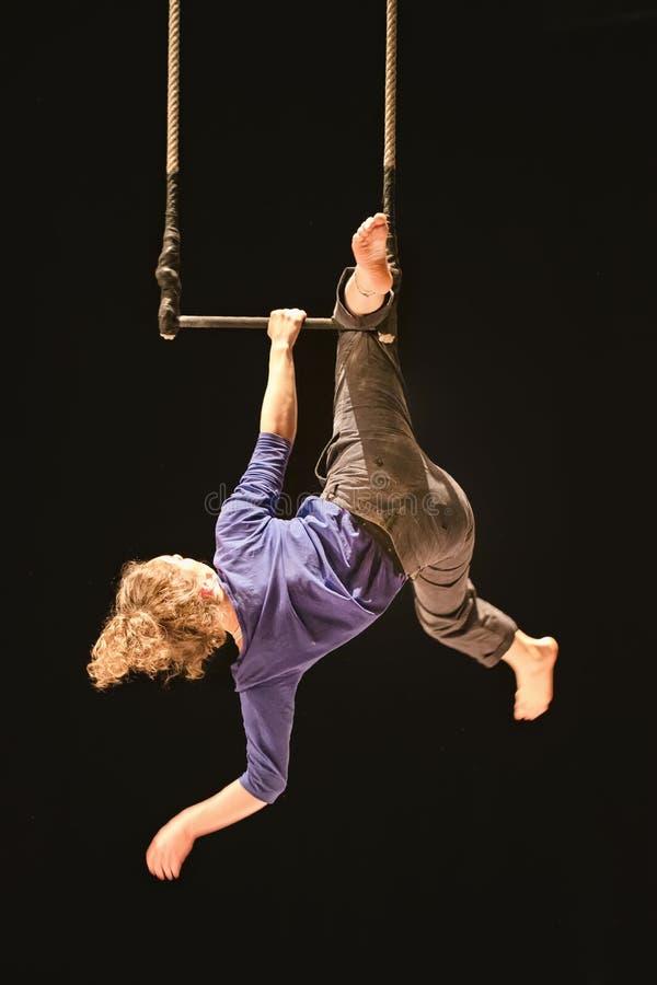 Het vrouwelijke acrobaat hangen op een schommeling in een circus stock foto's
