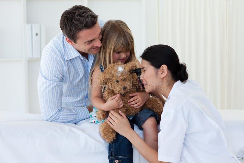 Het vrouwelijke arts spelen met een kindpatiënt stock fotografie