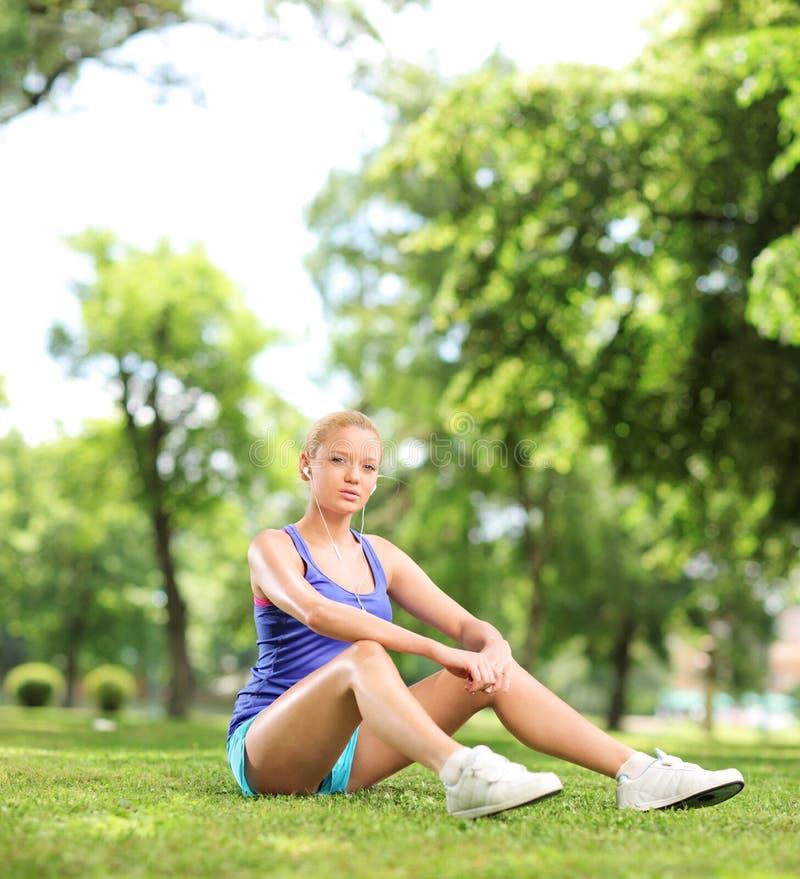 Het vrouwelijke atleet gezet rusten op gras in een park stock foto's