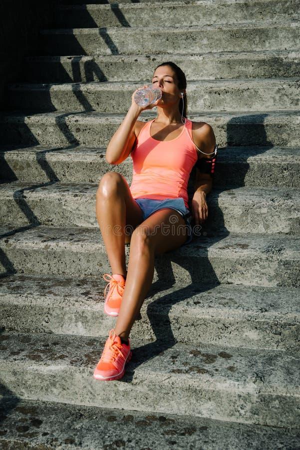 Het vrouwelijke atleet rusten en drinkwater na het uitoefenen royalty-vrije stock foto