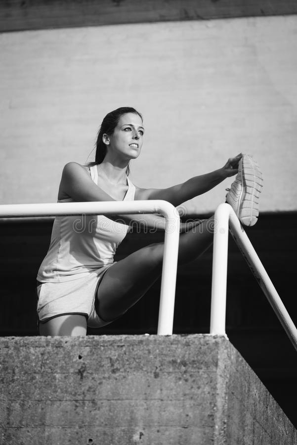 Het vrouwelijke atleet uitrekken zich voor het opwarmen royalty-vrije stock foto