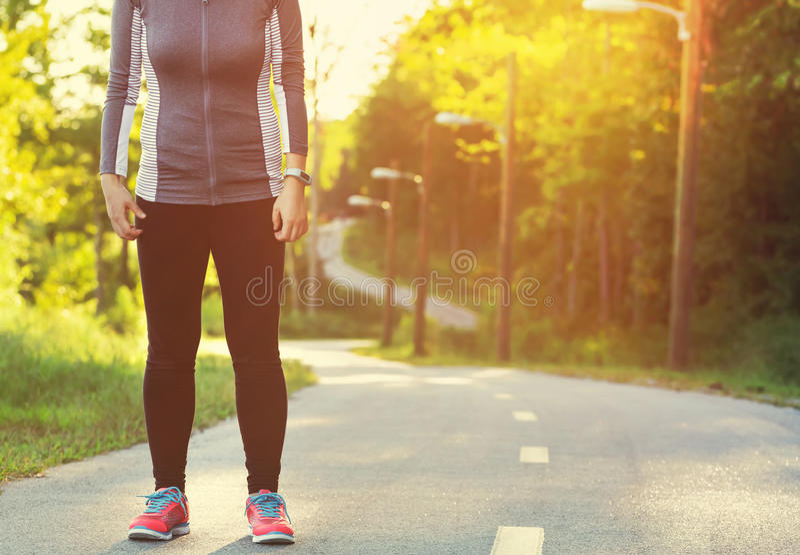 Het vrouwelijke atleet voorbereidingen treffen voor stoot op een bosweg aan stock foto's