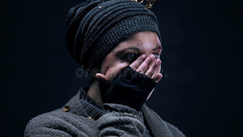 Het vrouwelijke bedelaar afvegen scheurt het behandelen van gezicht met hand, armoedehopeloosheid, misbruik royalty-vrije stock afbeeldingen